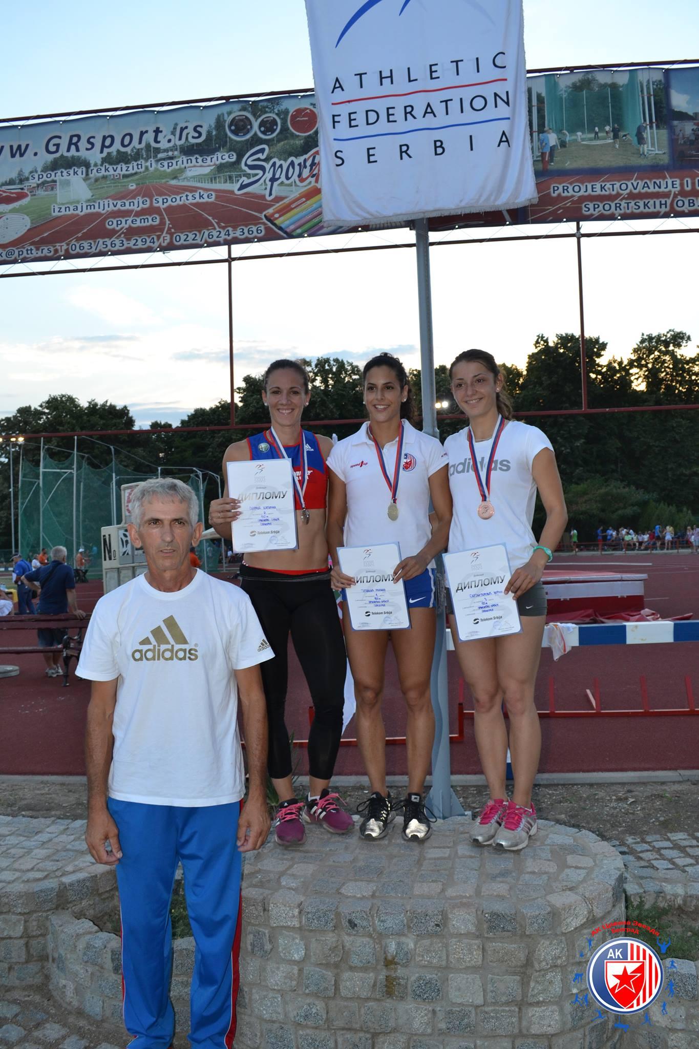 Pobedničko postolje Prvenstva Srbije u atletici. Sprint na 100 m. Prvo mesto Milana Tirnanić, drugo Katarina Sirmić, treće Zorana Barjaktarović. Medalje im stoje oko vrata, diplome u rukama.