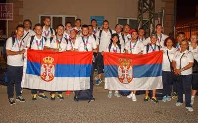 pančevački sportisti Specijalne olimpijade Srbije, učesnici i osvajači medalja na Svetskim igrama Specijalne olimpijade, sa zastavama Srbije u rukama stoje ispred škole Mara Mandić.
